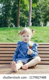 Close up portrait of a 3 years old girl eating ice cream