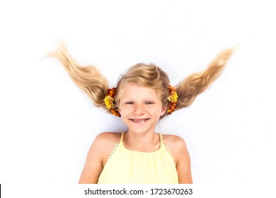 Close up portrait of 9 year old lovely teen girl lying against white background with crazy hair adorned with yellow and orange marigold flowers shot from birds perspective