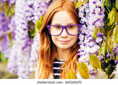 Close up portrait of adorable 9-10 year old red-haired kid girl posing in wisteria, wearing purple eyeglasses