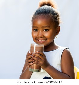Close up portrait of adorable African girl drinking milk chocolate drink.Isolated on light background.
