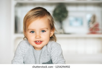 Close up portrait of adorable baby, looking straight at camera, blond hair, blue eyes