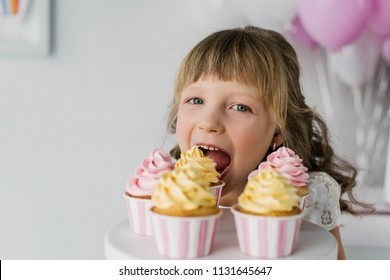 close up portrait of adorable birthday child eating cupcakes