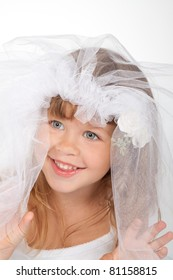 close up portrait of adorable little girl in a wedding dress the bride, happy smile 4 year child with brunette curly long hair, veil brides on head over white background.
