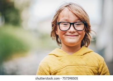 Close up portrait of adorable little kid boy wearing eyeglasses and yellow sweatshirt