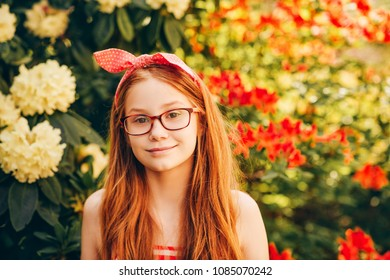 Close up portrait of adorable red-haired kid girl wearing eyeglasses, bright summer image