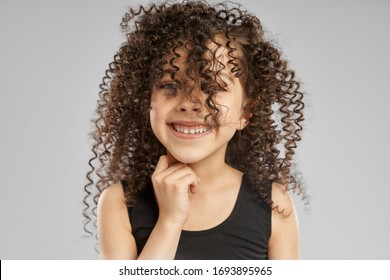 Close up portrait of adorable smiling girl in black sports top posing, isolated on gray studio background. Little female with curly brunette hair on face looking at camera and touching neck.