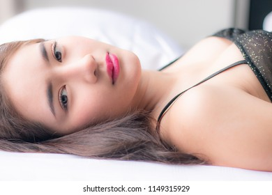 close up portrait adult beautiful sexy woman , asian thai female posing lying on white bed . brown color long curly hair . pretty smooth face and healthy skin . fashion nude style .