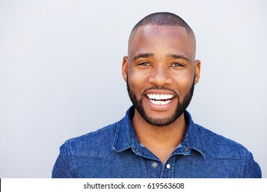Close up portrait of african american man laughing against gray wall