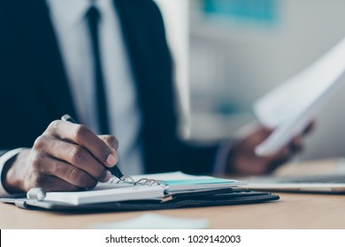 Close up portrait of african, american man's hand writing in organizer, planning his week, holding pencil in workplace, workstation