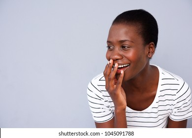 Close up portrait of african american woman smiling with her hand covering mouth on gray background