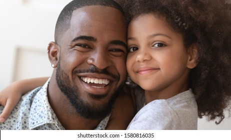 Close up portrait african five or six years old daughter cuddles handsome loving cheerful father relative people posing for camera smiling feels happy being together, daughterhood fatherhood concept