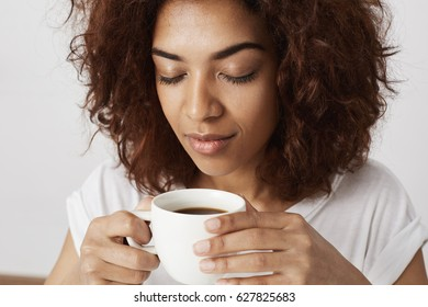 Close up portrait of african girl holding cup smelling coffee with closed eyes. Waking up in the morning is tough for adults.