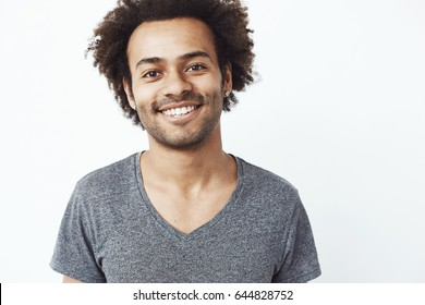Close up portrait of african guy smiling at camera, a student confident in his future career, or a head hunter dream standing over white wall.