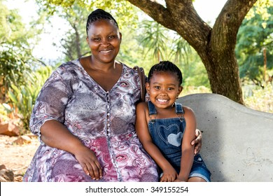 Close up portrait of african mother and child sitting on bench in park.
