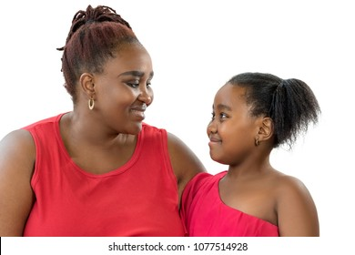 Close up portrait of African mother with little daughter looking at each other. Women dressed alike in red showing affection smiling at each other isolated on white background.