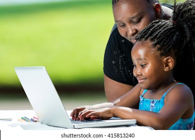 Close up portrait of african mother supervising school work of little daughter on laptop. Cute girl typing on laptop against green background outdoors.