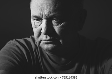 Close up portrait of aged man wearing t-shirt against black background - depression concept