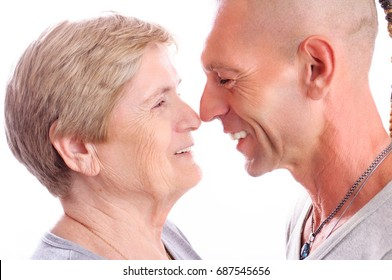 Close up portrait of aged mother and adult son, looking at each other, smiling. Concept: good relationships between two generations.