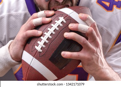 Close up portrait of aggressive American Football Player aggressive player biting his ball