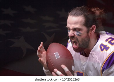 Close up portrait of aggressive American Football Player aggressive player biting his ball with US flag on background
