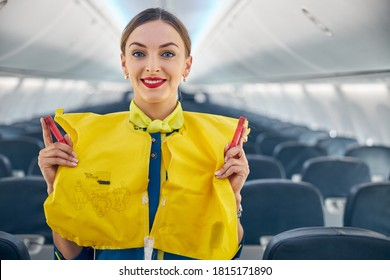 Close up portrait of air hostess demonstrating safety procedures to passengers prior to flight take off