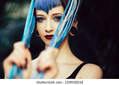 Close up portrait of alternative young woman with blue hair