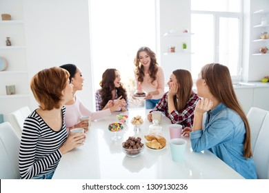 Close up portrait amazing beautiful she her diversity ladies sit round big white table in bright kitchen hold cups hot beverage try new recipe cakes girls day night holiday indoors