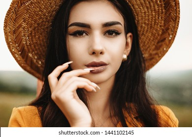 Close up portrait of an amazing woman with long dark hair wearing hat and looking at camera serious while touching her lips with fingers.