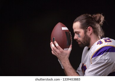 Close up portrait of American Football Player player who prays for game results to his ball