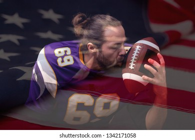Close up portrait of American Football Player who gently kiss the ball with flag of USA on background
