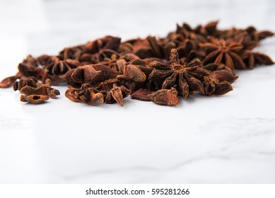 Close up portrait of anise seeds on white marble background