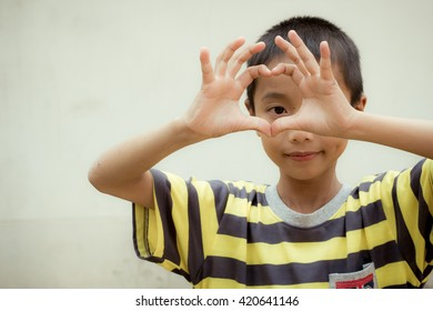 Close up portrait of Asian boy, Make heart from his hands.