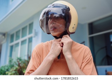 Close up portrait of asian thai woman wearing helmet before riding motor bike. Safety first before hit the road.