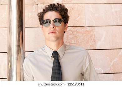 Close up portrait of an aspirational businessman wearing shades and leaning on a modern building in the city.
