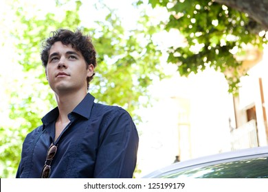 Close up portrait of an aspirational businessman wearing an elegant shirt and leaning on a car, looking away with trees in the background.