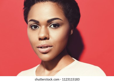 Close up Portrait of attractive African American young woman with perfect skin and natural make up. Beautiful brunette model. Skin and Face Care Concept. Looking on camera against red background