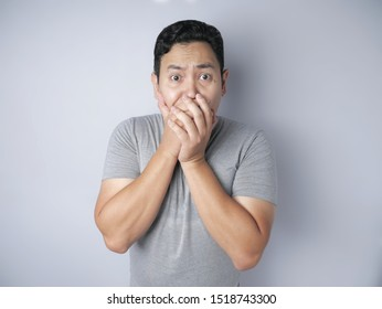 Close up portrait of attractive Asian young man closing his mouth with fingers. Worried gesture, can't say anything. Shocked surprised to hear bad news or gossip, looking at camera