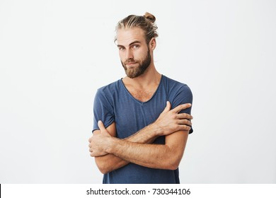 Close up portrait of attractive bearded man with good-looking hairstyle crossing hands on chest, looking at camera with flirty expression.
