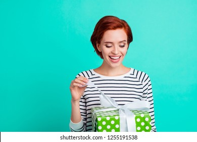 Close up portrait of attractive beautiful she her lady holding large gift box in hands unboxing it  wondered what inside wearing white striped sweater isolated on teal background