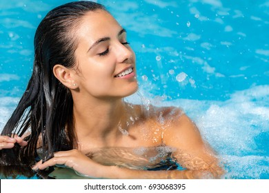 Close up portrait of attractive brunette relaxing in spa jacuzzi. Woman with relaxed face expression touching hair.