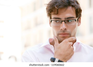 Close up portrait of an attractive businessman being thoughtful while standing next to office buildings in a classic city square.