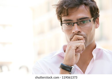 Close up portrait of an attractive businessman being worried and thoughtful while standing next to office buildings in a classic city square.