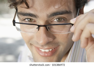 Close up portrait of an attractive businessman wearing spectacles and smiling, outdoors.
