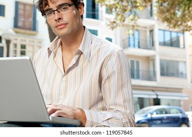 Close up portrait of an attractive businessman wearing glasses and using a laptop computer in the city, outdoors.