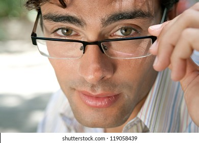 Close up portrait of an attractive businessman wearing glasses and looking at the camera in the city, outdoors.