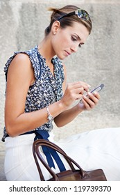Close up portrait of an attractive businesswoman sitting down on stone steps in the city, using a smart phone.