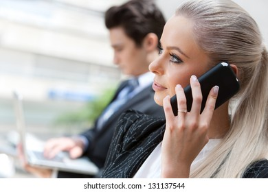Close up portrait of attractive businesswoman talking on smart phone at meeting.
