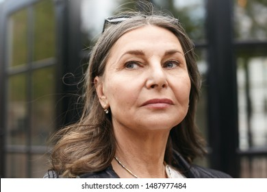 Close up portrait of attractive Caucasian female pensioner with loose gray hair and wrinkles having serious facial expression, looking away, posing outdoors with modern building in blurred background