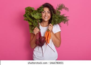 Close up portrait of attractive caucasian smiling woman isolated on rose studio background, wearing white casual t shirt, holding beets and carrots in hands. Raw dood eatinf and healthy eating concept