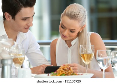 Close up portrait of attractive couple looking at smart phone at restaurant.